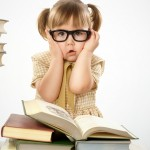 Little girl surrounded by books wearing black glasses, back to school concept
